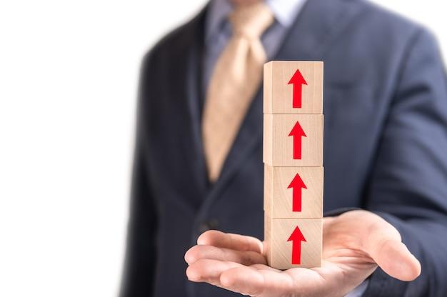 ビジネスマンは白い背景で隔離上向き矢印と木製の立方体を保持します