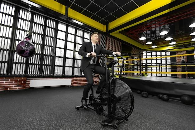 Бизнесмен в черном костюме занимается на велотренажере в боксерском клубе.