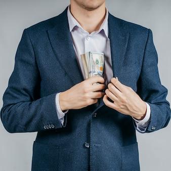 Бизнесмен в черном костюме кладет деньги в карман