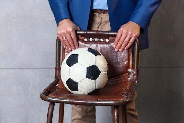 青いジャケットを着たビジネスマンが壁の近くに立って、サッカーが椅子に横たわっています