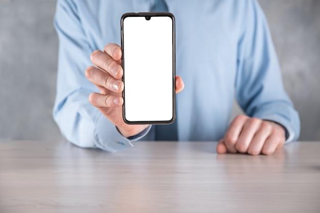 Бизнесмен в голубой рубашке на рабочем месте за столом, держащим мобильный телефон, смартфон с белым экраном. экран перед камерой. макет. концепция технологии, связи, коммуникации.