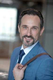 Бизнесмен в синем костюме с сумкой