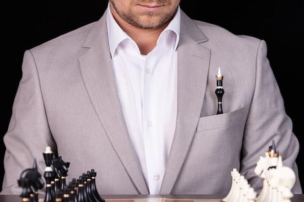 ポケットにチェスの駒を持ったビジネススーツを着たビジネスマン
