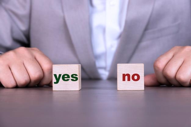 ビジネスマンは、灰色のスーツを着て、「はい」と「いいえ」の単語が付いた立方体を持っています Premium写真