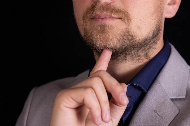 灰色のスーツを着たビジネスマンは考えています。ビジネスコンセプト、アイデア。