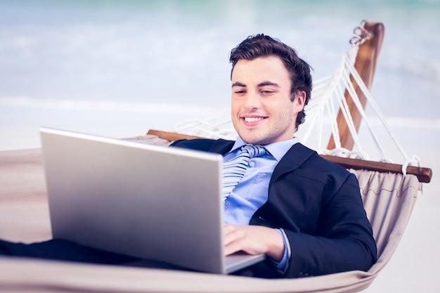 Бизнесмен в гамаке, используя ноутбук