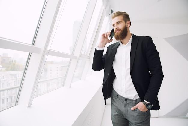 携帯電話と話している現代のオフィスのビジネスマン