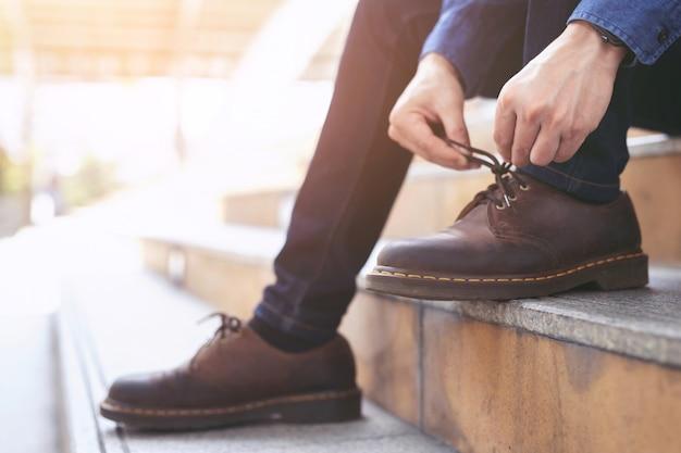 格子縞のシャツのジーンズのビジネスマンは、階段の背景に座っている茶色の革の靴を履いて靴ひもを結びます。メンズスタイル。