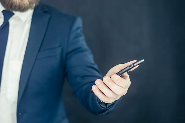 셔츠와 손에 스마트 폰으로 파란색 재킷에 사업가.