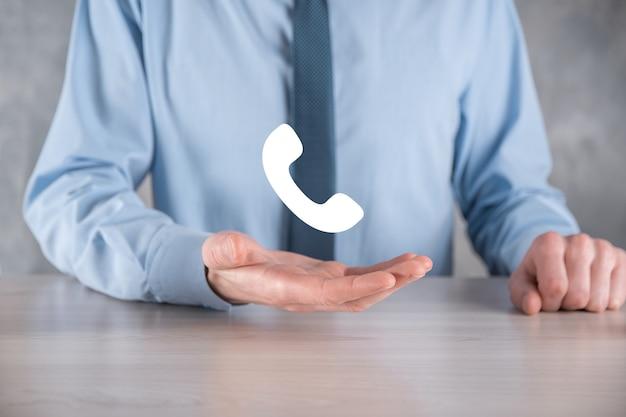 灰色の表面にネクタイとシャツを着たビジネスマンは、電話のアイコンを保持します。