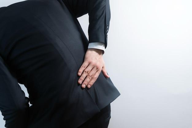 腰痛のあるスーツを着たビジネスマン。腰を握っている手で痛みでかがむ