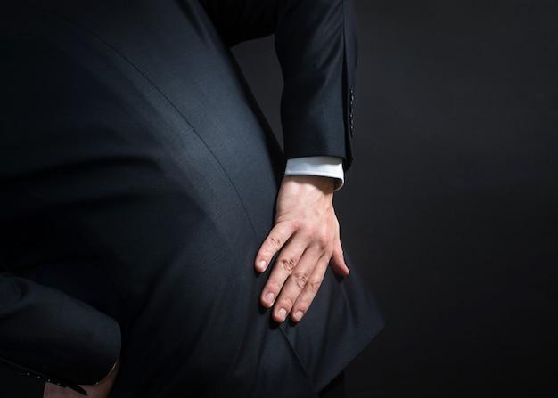 腰痛のあるスーツを着たビジネスマン。