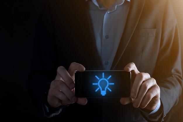 スーツを着たビジネスマンが電球を手にスマートフォンを持っています