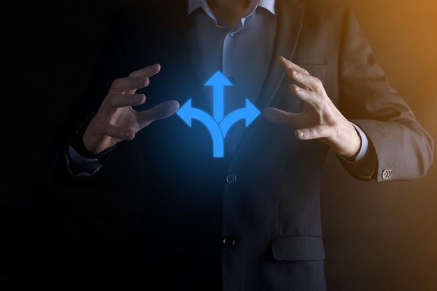 スーツを着たビジネスマンは、反対方向を指す矢印で示された 3 つの異なる選択肢から選択しなければならない疑いのある 3 つの方向を示すサインを持っています。