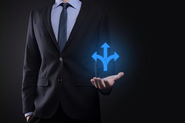 Бизнесмен в костюме держит знак, показывающий три направления. в сомнениях, приходится выбирать между тремя различными вариантами, обозначенными стрелками, указывающими в противоположном направлении. три способа выбрать