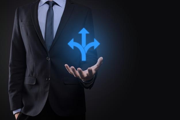 소송에서 사업가 세 방향을 보여주는 기호를 보유하고있다. 반대 방향 개념을 가리키는 화살표로 표시된 세 가지 다른 선택 중에서 선택해야합니다. 선택하는 세 가지 방법
