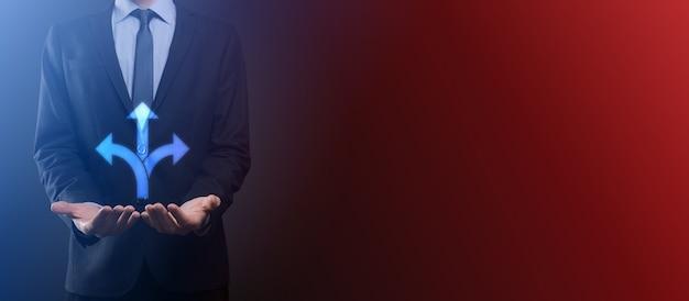 スーツを着たビジネスマンは、反対方向の概念を指す矢印で示される3つの異なる選択肢から選択する必要がある疑いのある3つの方向を示す看板を持っています3つの選択方法