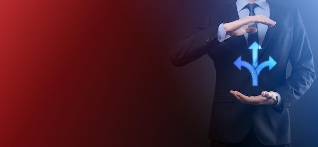スーツを着たビジネスマンは、反対方向を指す矢印で示される 3 つの異なる選択肢から選択しなければならないという 3 つの方向を示すサインを持っている 3 つの方法を選択する