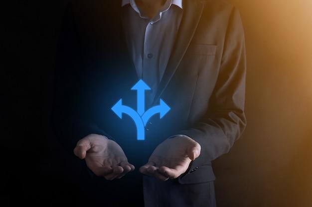 スーツを着たビジネスマンは、反対方向を指す矢印で示される3つの異なる選択肢から選択する必要があるかどうか疑わしい3つの方向を示す看板を持っています