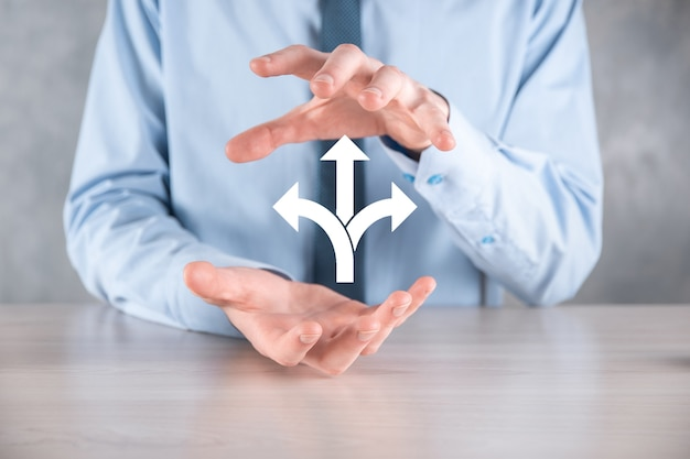 スーツを着たビジネスマンは、3つの方向を示す看板を持っています。疑わしい場合は、矢印で示された3つの異なる選択肢から選択する必要があります