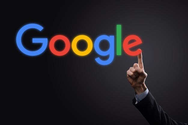 어두운 배경에 양복을 입은 사업가는 google 로고 비문을 보유하고 있습니다. google은 세계에서 가장 인기있는 검색 엔진입니다.