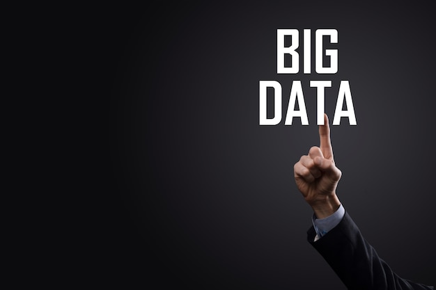 Бизнесмен в костюме на темном фоне держит надпись big data. концепция сервера сети хранения данных онлайн. представление социальной сети или бизнес-аналитики.