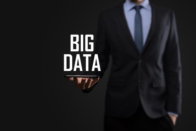 暗い背景にスーツを着たビジネスマンは、碑文ビッグデータを保持しています。ストレージネットワークオンラインサーバーの概念。ソーシャルネットワークまたはビジネス分析の表現。