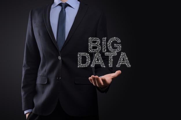 暗い背景にスーツを着たビジネスマンは、碑文ビッグデータを保持しています。ストレージネットワークオンラインサーバーの概念。ソーシャルネットワークまたはビジネス分析の表現