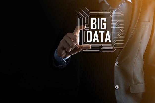 어두운 배경의 정장을 입은 사업가는 big data라는 글자를 가지고 있습니다. 스토리지 네트워크 온라인
