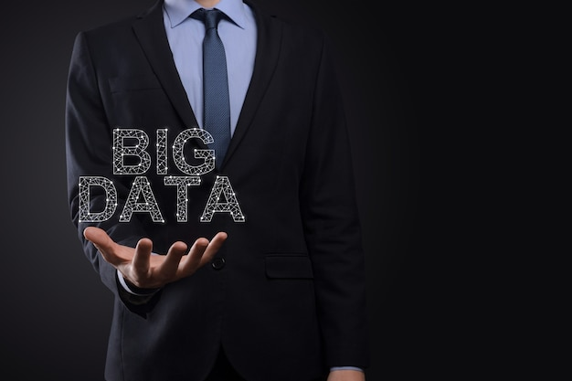 暗い表面でスーツを着たビジネスマンは、碑文ビッグデータを保持します
