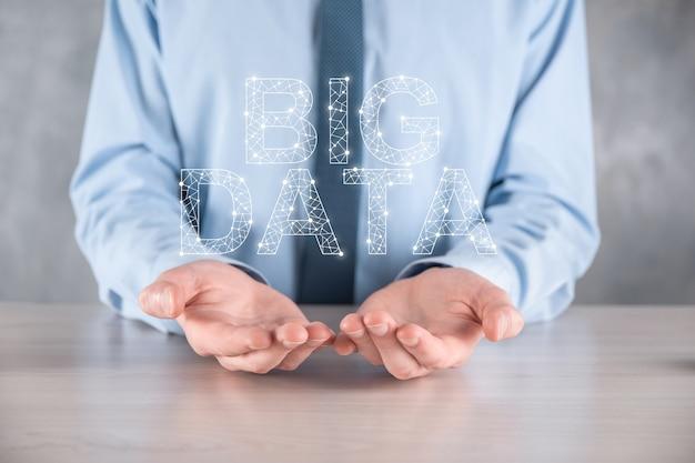 暗い壁にスーツを着たビジネスマンが、ビッグデータの碑文を持っている。ストレージ ネットワーク オンライン サーバー コンセプト。ソーシャル ネットワークまたはビジネス分析の表現。