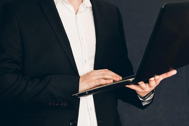 Бизнесмен в костюме с ноутбуком в руках. человек с ноутбуком в руках