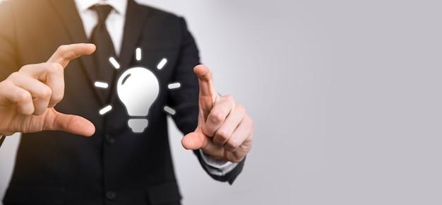 彼の手に電球を持つスーツを着たビジネスマン。輝くアイデアのアイコンを手に持っています。テキストのための場所で