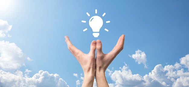 그의 손에 전구와 소송에서 사업가. 그의 손에는 빛나는 아이디어 아이콘이 있습니다. 텍스트에 대 한 장소.