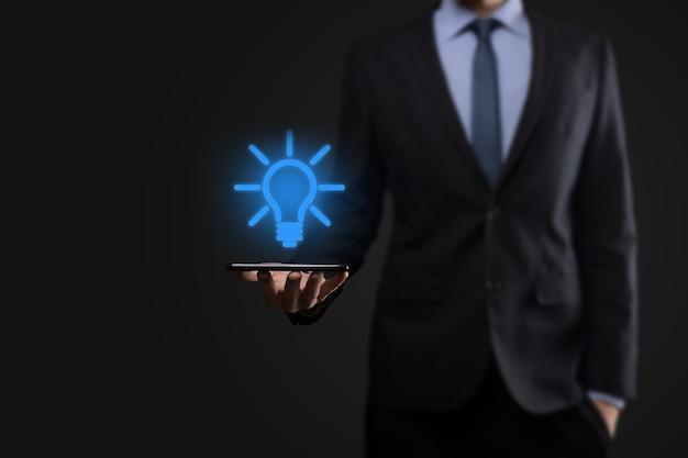 Бизнесмен в костюме с лампочкой в руках. в руке держит светящийся значок идеи. с местом для текста.