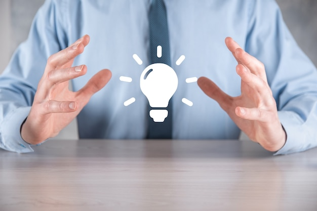 그의 손에 전구와 소송에서 사업가. 그의 손에 빛나는 아이디어 아이콘을 들고 있습니다. 텍스트를위한 장소.