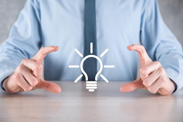 彼の手に電球を持つスーツを着たビジネスマン。輝くアイデアのアイコンを手に持っています。テキストのための場所で。