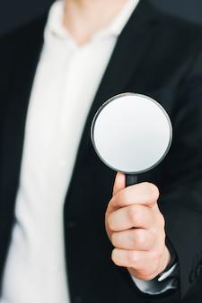 Бизнесмен в костюме с увеличительным стеклом в руке. мужчина с увеличительным стеклом в руке