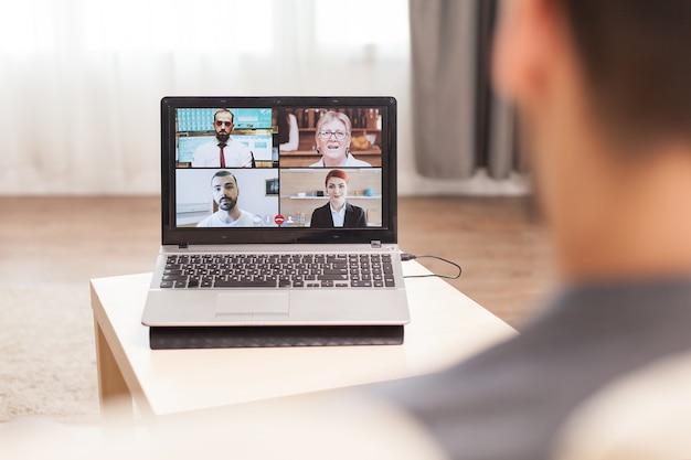 検疫中に自宅で仕事をしているときに彼のチームとのビデオ会議でビジネスマン。