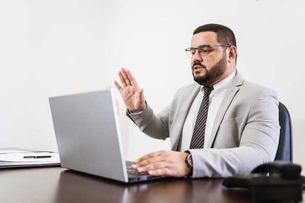 Бизнесмен в видеоконференции с ноутбуком и документами на своем столе, консультант адвокат концепции.