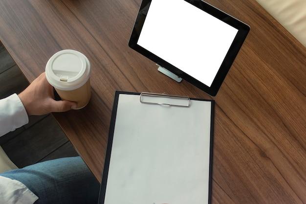 그의 손에 디지털 태블릿 흰 셔츠에 사업가 사무실에서 계약에 서명합니다. 한 잔의 커피와 나무 테이블에 펜으로 문서와 직장.