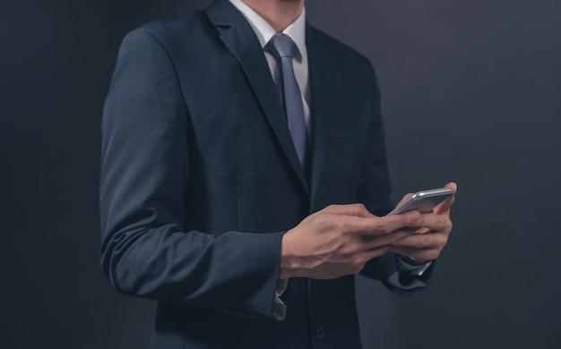검은 배경에 스마트폰을 들고 검은 양복과 넥타이에 사업가.