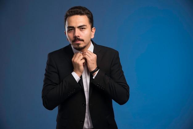 Бизнесмен в черном костюме, застегивая рубашку.