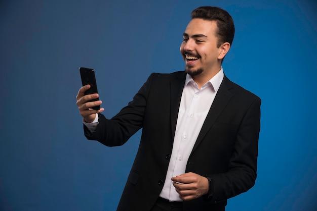 彼の電話をチェックしている黒いスーツのビジネスマン。