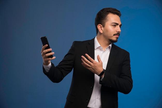 그의 전화를 확인하는 검은 양복에 사업가입니다.
