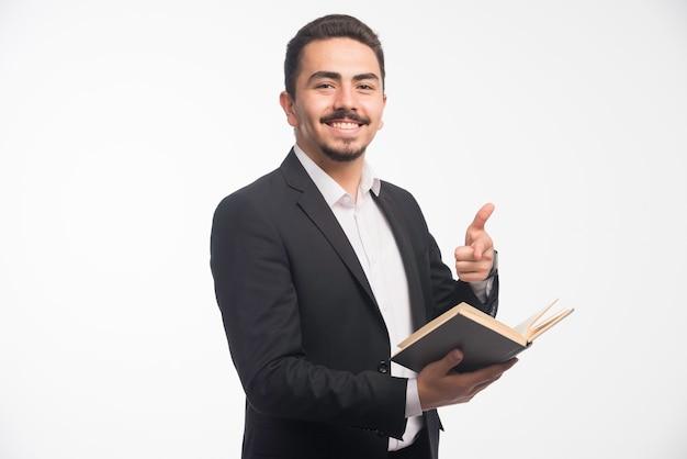 彼のタスクリストを保持し、親指を立てる黒いスーツのビジネスマン。