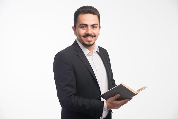 Бизнесмен в черном костюме держит его список задач и улыбается.