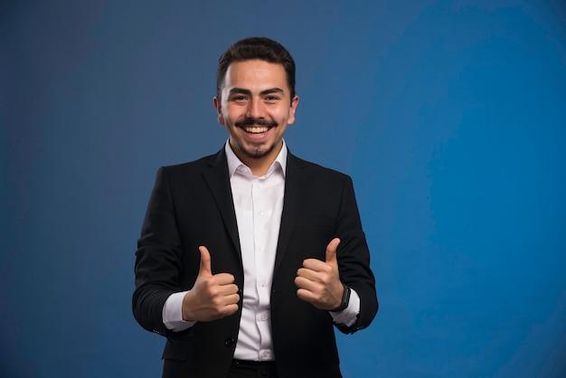 Бизнесмен в черном костюме делает большой палец вверх знак.