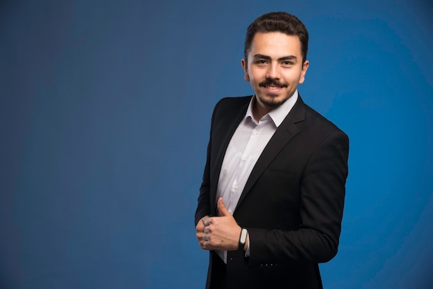 黒のスーツを着たビジネスマンは親指を立てます。
