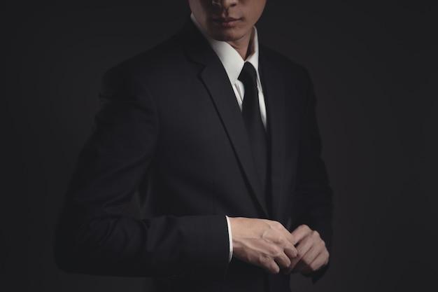 Бизнесмен в черном костюме на черном